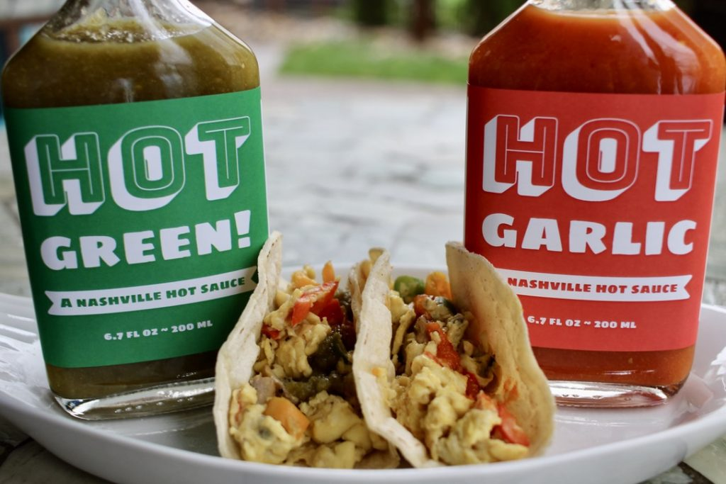 two breakfast tacos with hot green and hot garlic beside them